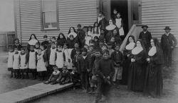 Photographie en noir et blanc. Foyer fédéral d'Inukjuak (Port Harrison), groupe d'élèves, religieuses et hommes autochtones posant devant l'école, Québec, vers 1890.